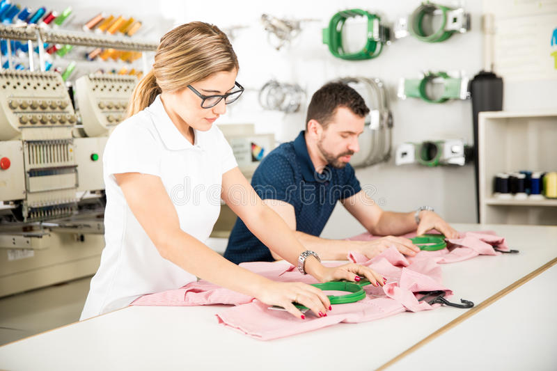 Getting garments ready for embroidery. Couple of workers getting some garments ready for embroidery in a textile factory stock photo