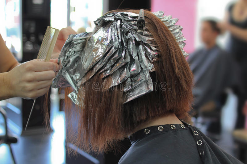 Getting highlights at the salon. Teen girl gets full foil highlights at a professional salon stock photos