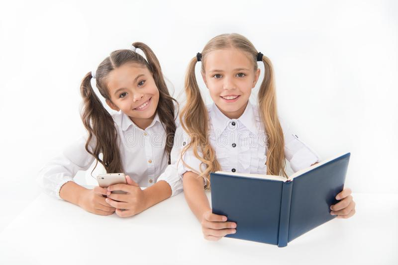 Getting information. Modern data storage instead big paper book. Little girls read paper book and ebook smartphone royalty free stock photo