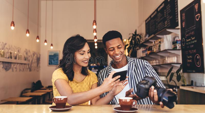 Getting inspiration from friend`s content. Young women taking pictures from male friends digital camera. Young men and women sitting at coffee shop with smart royalty free stock photo