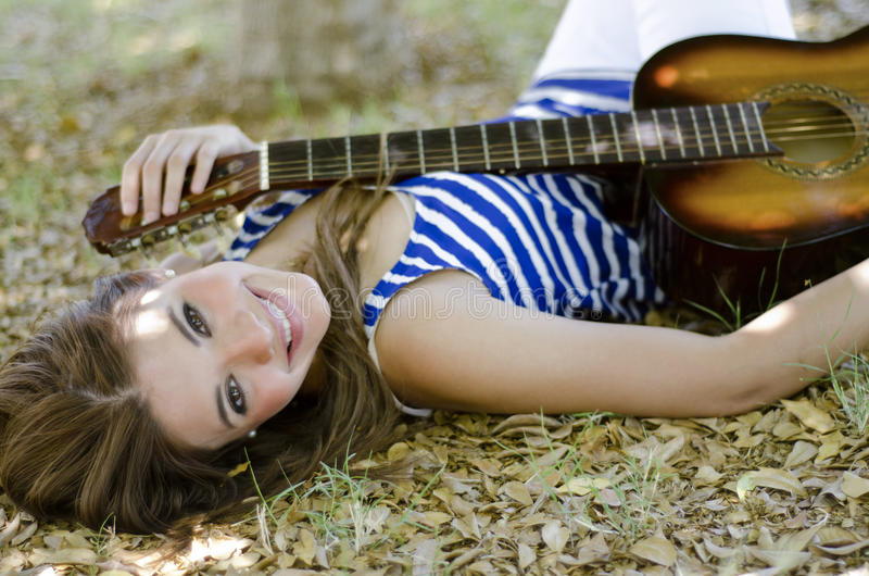 Getting inspired at a park. Beautiful young woman holding a guitar and relaxing at the park stock image