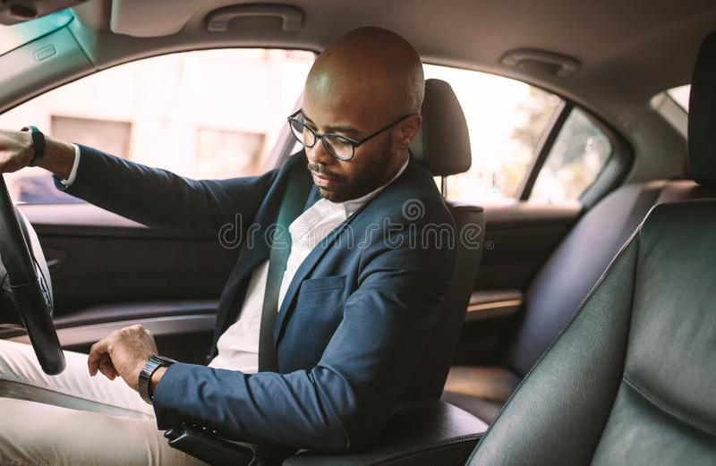 Getting late for work. Young african businessman driving a car and checking . Male driver sitting in car in traffic jam and looking at wristwatch royalty free stock photo