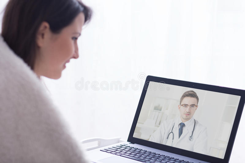 Getting an on-line advice. Doctor giving an advice to his patient using the technological solutions royalty free stock images