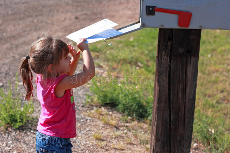 Getting the Mail. Cute toddler girl getting the mail out of a rural mailbox