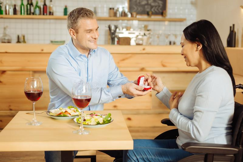 Exuberant man proposing to a disabled woman. Getting married. Good-looking exuberant blond men smiling and proposing to his beautiful delighted handicapped women stock photos
