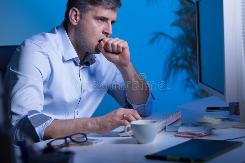 Getting more and more sleepy. Shot of an office worker sitting in his workplace and yawning royalty free stock image