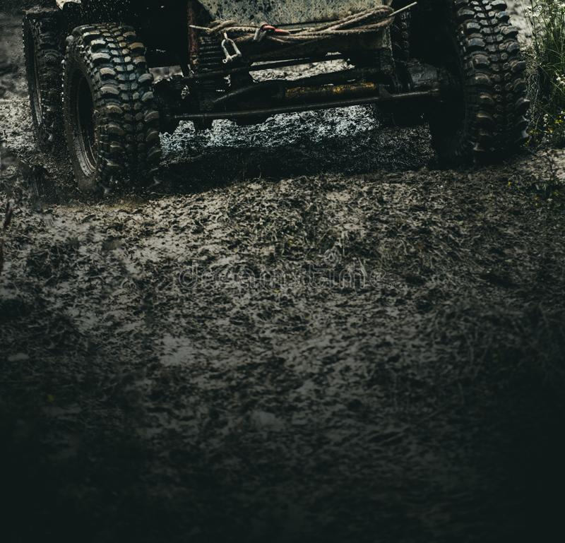 Getting the most out of the off road adventure. Car wheels on steppe terrain splashing with dirt. Car racing offroad. Offroad car in action. Dirty car drive on royalty free stock photography