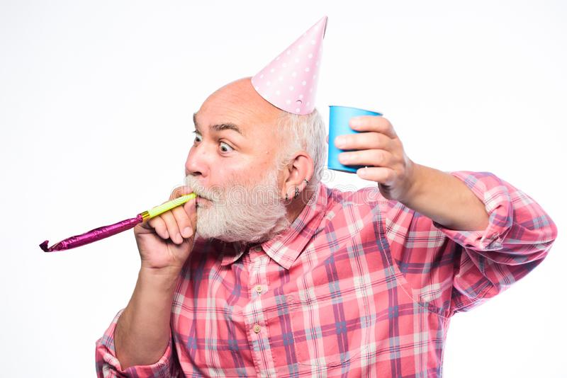 Getting older is still fun. Elderly people. Man bearded grandpa with birthday cap and drink cup. Birthday crazy party royalty free stock photography