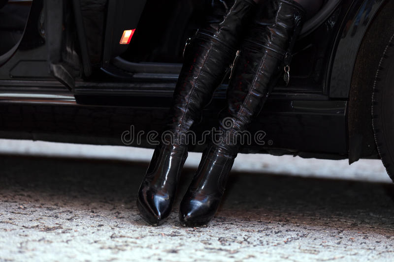 Getting out of the car. Unrecognizable girl in boots is getting out of the car stock photography