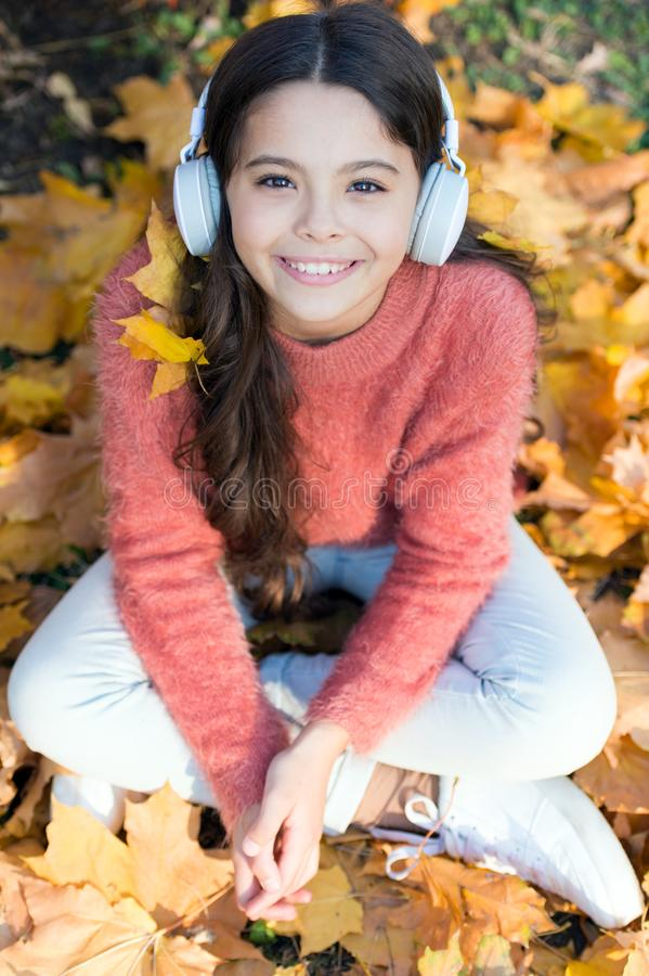 Getting pleasure in simple things. Little girl listen to music. Happy little girl in autumn. Happy child wear headphones royalty free stock photography