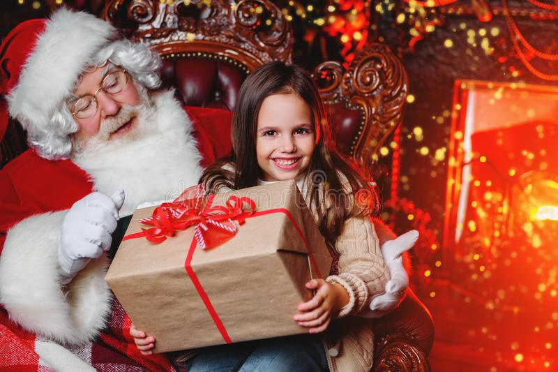 Getting present from santa. A happy young girl is sitting with a present near Santa Claus at home. Merry Christmas and Happy New Year stock photography