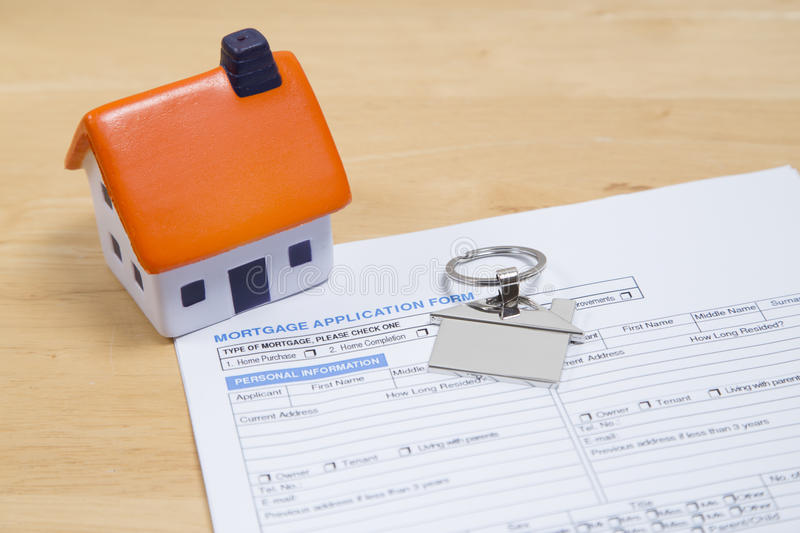 Getting on the property ladder. Foam house with chrome key ring sitting on mortgage application papers royalty free stock photo