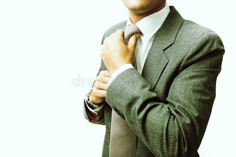 Getting ready. Businessman fastening tie, getting ready for work, cross-processed royalty free stock photos