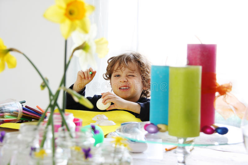 Getting ready for Easter. A child (boy) is painting eggs and getting ready for Easter stock photo