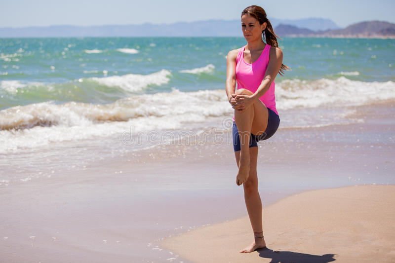 Getting ready for a run. Beautiful young brunette doing some stretching exercises before running at the beach royalty free stock photos