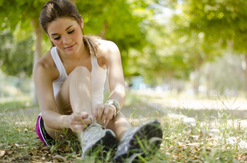 Getting ready for running. Cute young woman tying her shoelaces and getting ready for running at the park royalty free stock image