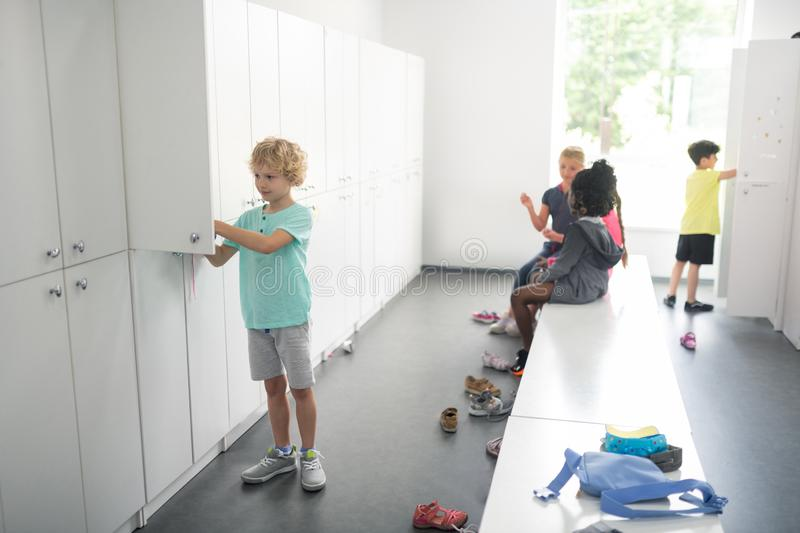 Children in a changing room preparing for sports. Getting ready. School children in a changing room preparing for their sports lesson royalty free stock photos