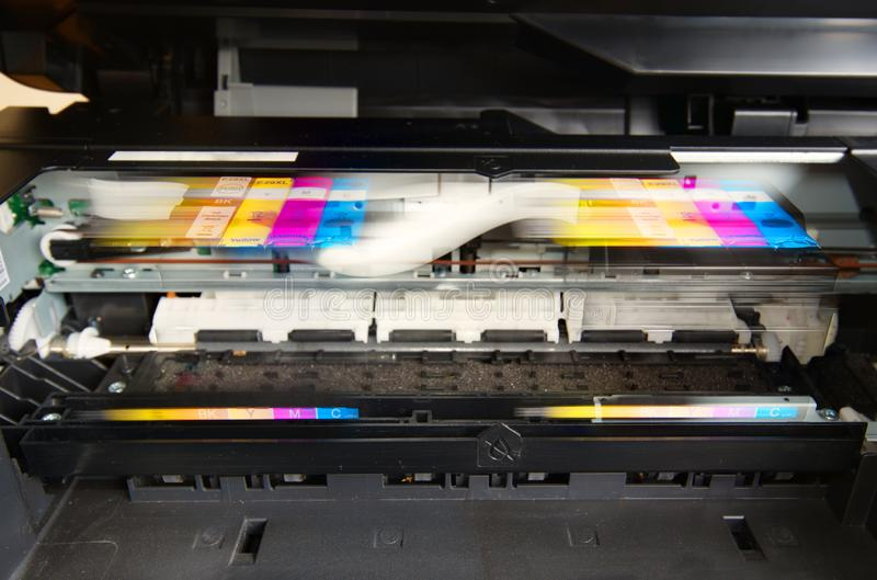 Colour printer ink cartridges in motion Close up. Getting ready to print. Close up of four generic ink cartridges in a colour printer, moving along the printer royalty free stock photos