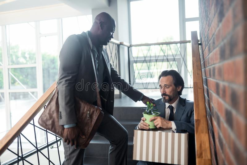Dark-skinned friend speaking with colleague after getting redundant. After getting redundant. Dark-skinned pleasant friend speaking with colleague after getting stock photos