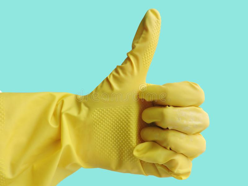 Getting started cleaning. Yellow rubber gloves for cleaning on blue background stock photos