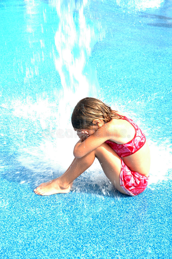 Getting Wet Splash. Little girl sits on the ground as the bucket of water dumps on her and splashes to the ground royalty free stock photo