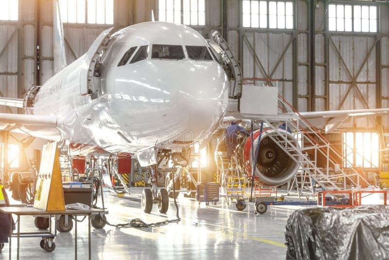 Getto degli aerei su mantenimento della riparazione del controllo della fusoliera e del motore nel capannone dell'aeroporto immagini stock libere da diritti