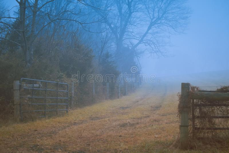 Gettysburg, PA/EUA - em dezembro de 2018: Uma cerca de madeira velha ao longo da estrada de terra místico na névoa Conceito do ou imagens de stock