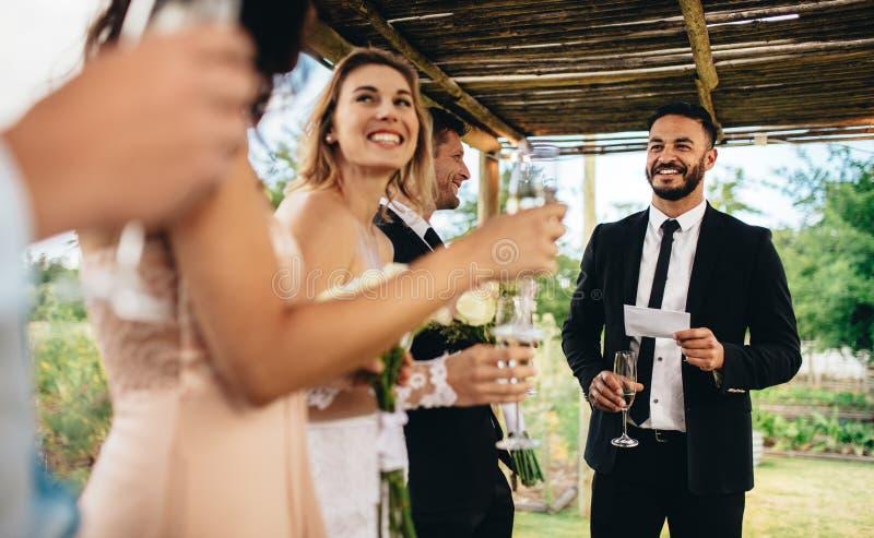 Getuige die toespraak voor toost uitvoeren bij huwelijksontvangst stock afbeelding