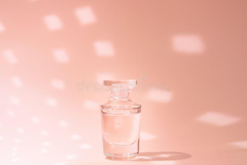 Geur in parfumfles op roze achtergrond met exemplaarruimte stock foto's