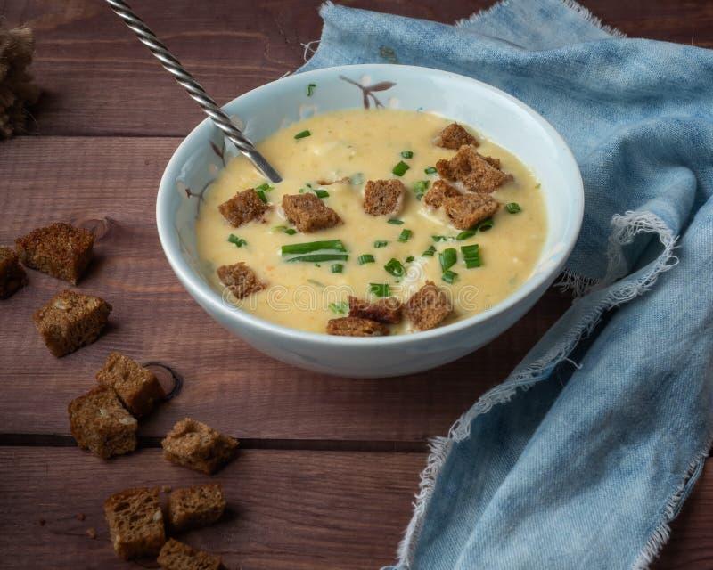 Geurige die groentesoep met room en kaas in een diepe blauwe plaat met een lepel op een blauw die denimservet wordt fijngestampt, royalty-vrije stock afbeeldingen