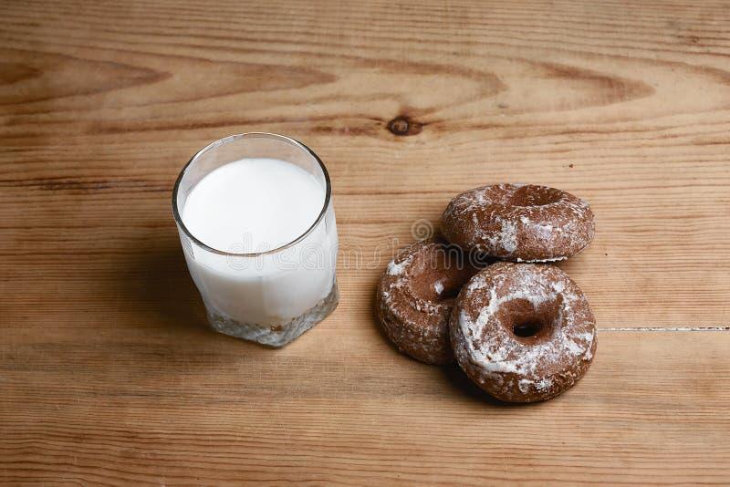 Geurige honingspeperkoeken, cakes en een glas melk op een houten achtergrond, hoogste mening, natuurvoeding stock fotografie