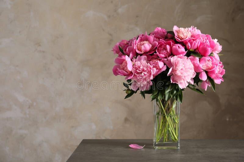 Geurige pioenen in vaas op lijst tegen kleurenachtergrond De mooie Lente royalty-vrije stock foto
