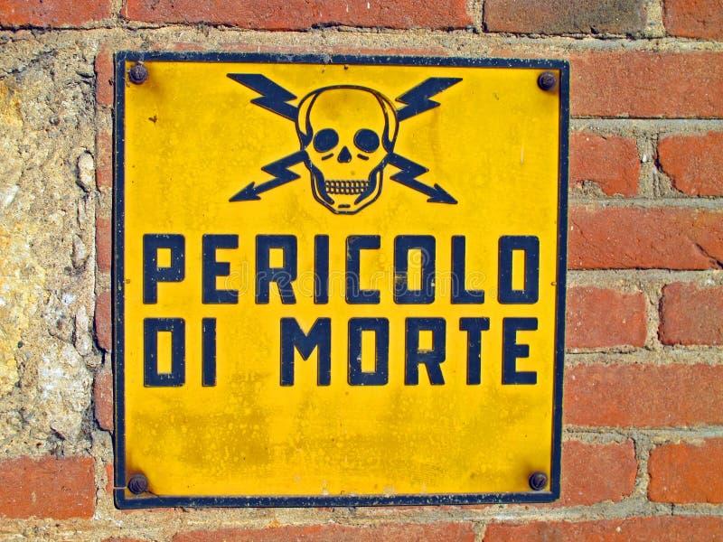 Gevaar van doodstekens met schedel en gekruiste knekels in Itali worden geschreven die royalty-vrije stock afbeelding