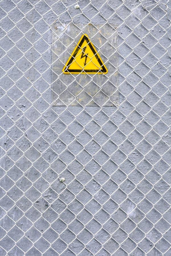 Gevaar van elektrocutie geel teken op grijs Hoogspanningswaarschuwingsbord stock foto
