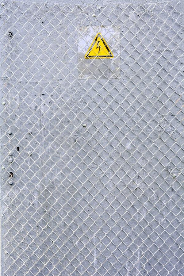 Gevaar van elektrocutie geel teken op grijs Hoogspanningswaarschuwingsbord stock foto's