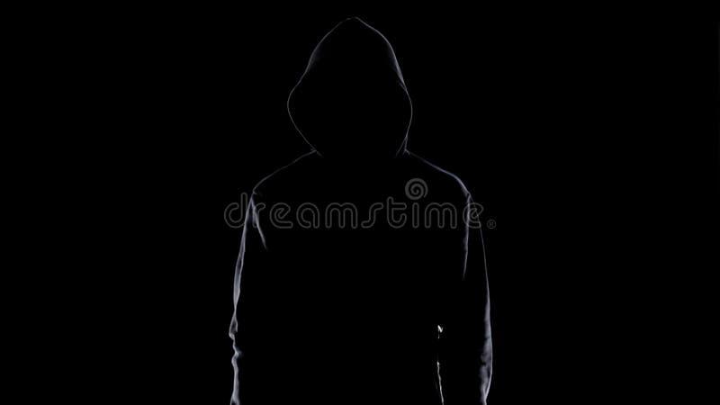 Gevaarlijk anoniem mannetje in nachtduisternis, enge terrorist die voor misdaad voorbereidingen treffen stock foto
