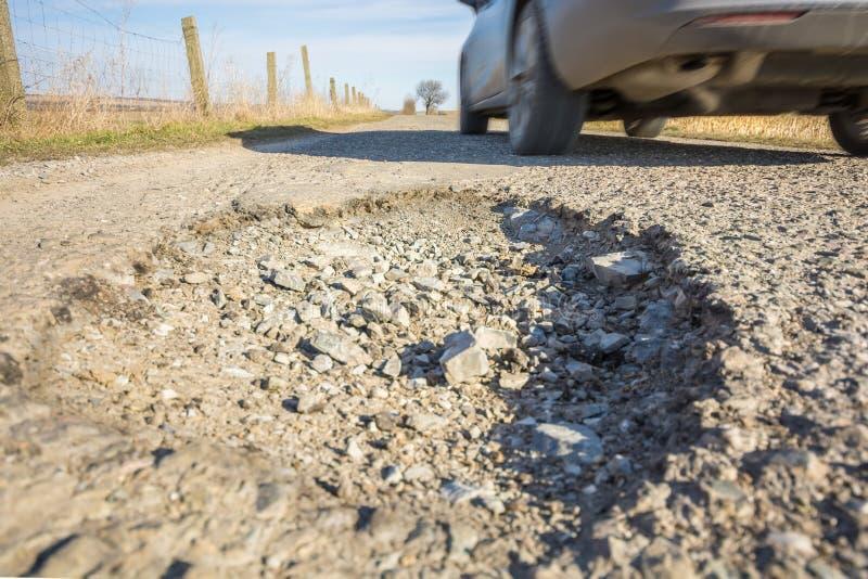 Gevaarlijk gat in de asfaltoppervlakte van een weg met het overgaan van auto stock foto's