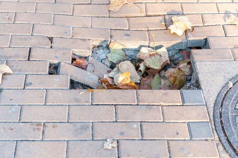 Gevaarlijk gat voor voetgangers op beschadigde stoep met gebroken bakstenen op de stedelijke stadsstraat royalty-vrije stock afbeeldingen