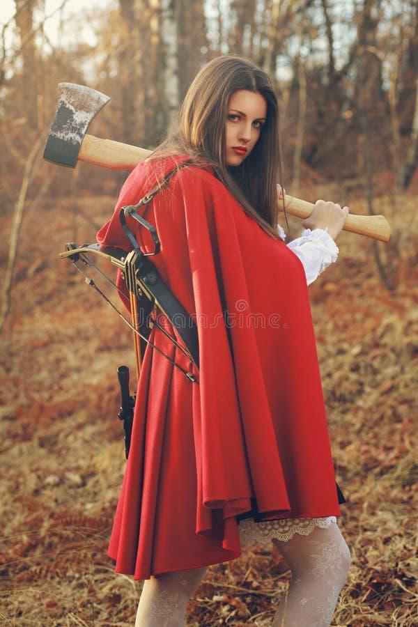 Gevaarlijk Weinig rode berijdende kap met bijl stock foto