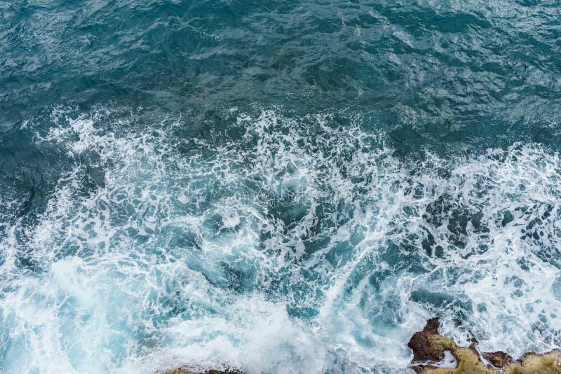 Gevaars diepe blauwe oceaan met golf die op rotskust verpletteren met spr stock afbeeldingen