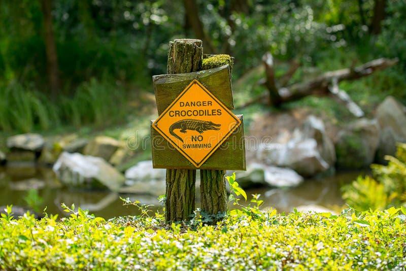 Gevaarskrokodillen, geen die het zwemmen - waarschuwingsbord op de kust van het meer wordt gevestigd royalty-vrije stock fotografie