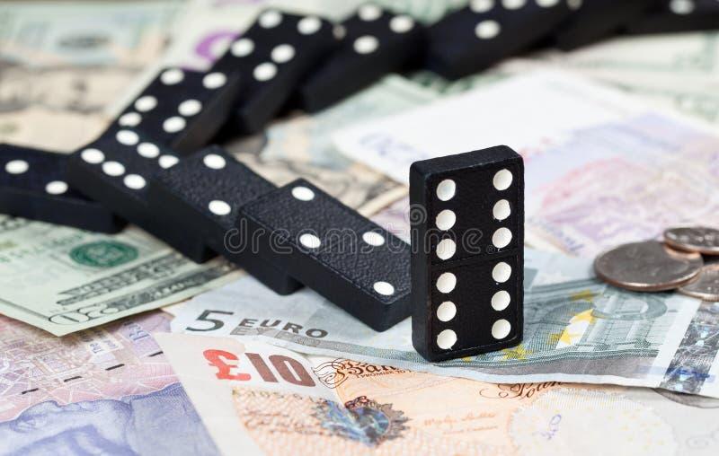Gevallen domino's op bankbiljetten stock afbeeldingen