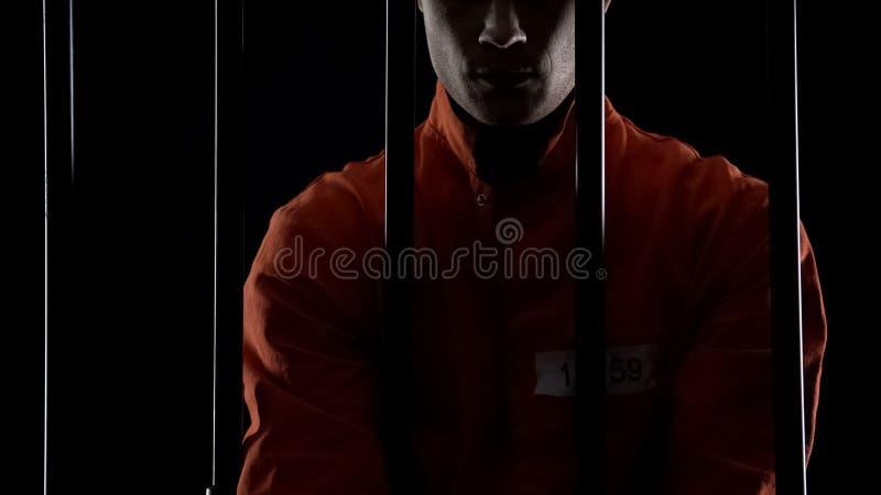 Gevangene in oranje eenvormige achter de tralies status, straf voor toegewijde misdaad royalty-vrije stock foto's