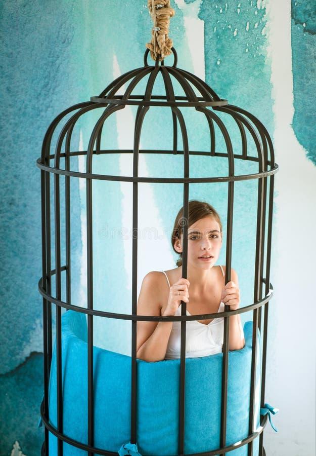 Gevangene in vrees modern meubilairontwerp en huiscomfort manierslaaf in gevangenschap van schoonheid vrouw binnen ijzerkooi royalty-vrije stock fotografie