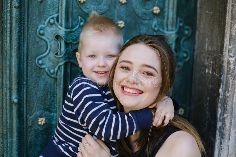 Gevend mamma die met haar weinig zoon koesteren lach Concept liefde, familie, opvoeding en levensstijl stock foto