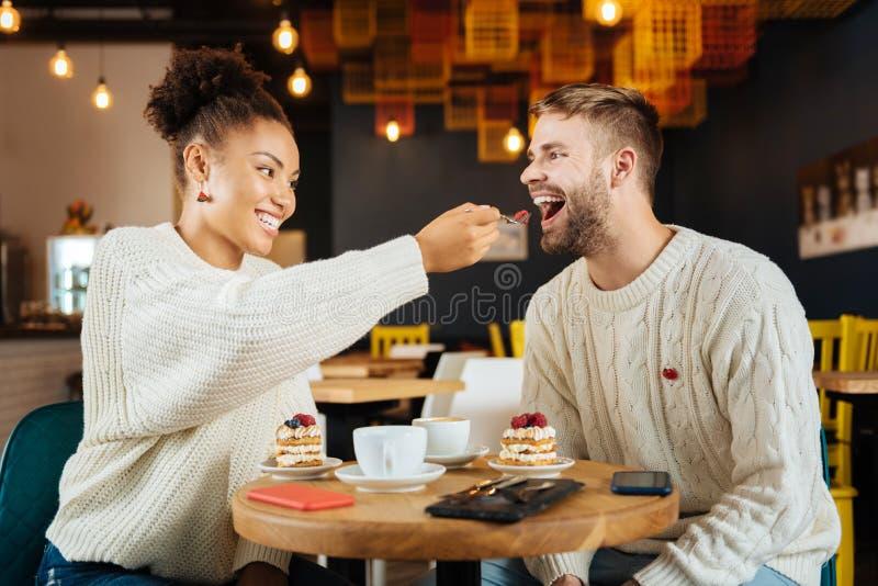 Gevend meisje die stuk van cake haar echtgenoot geven stock afbeelding