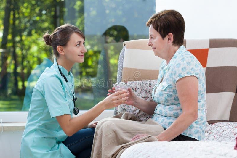 Gevend patiënt een glas water stock foto's