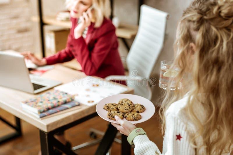 Gevend weinig dochter die chocoladekoekjes en citroenwater geven royalty-vrije stock foto's