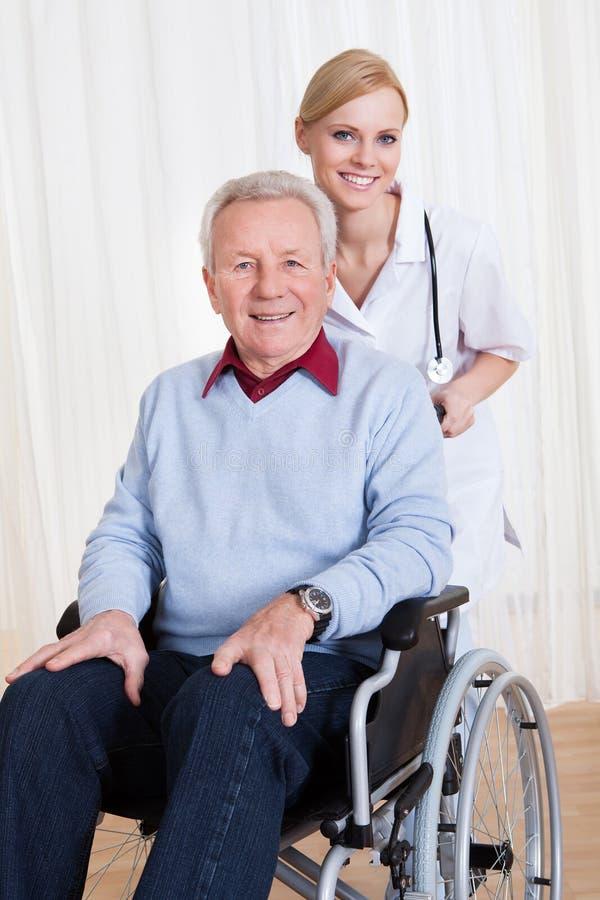 Gevende arts die gehandicapte patiënt helpen stock afbeeldingen