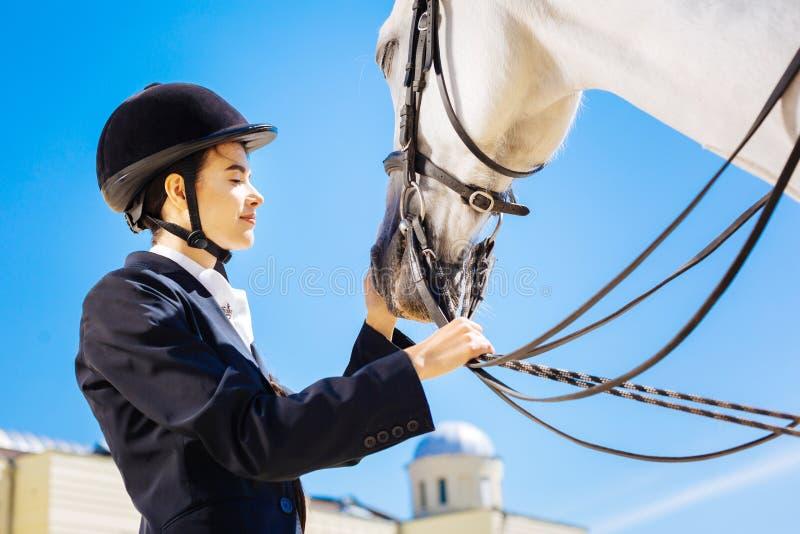 Gevende houdende van amazone die haar wit paard kalmeren stock afbeeldingen